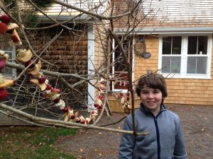 Simon stands outside the cabin with cranberry garland in the tree